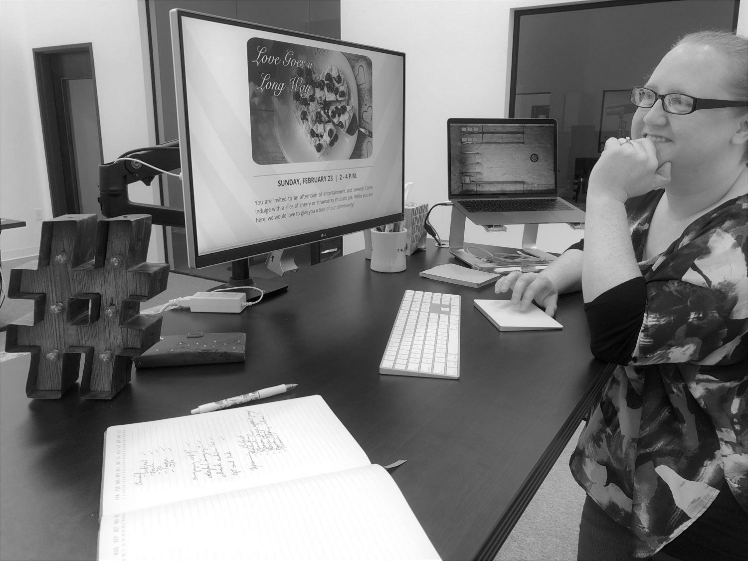 Meredith of Craft & Communicate stands at desk looking at a marketing eblast