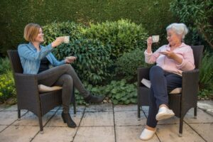 Craft & Communicate | Senior drinking tea with caregiver